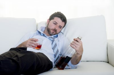 alcoholic Businessman in shirt and tie drunk on couch