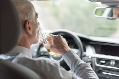 Man drinking alcohol and driving