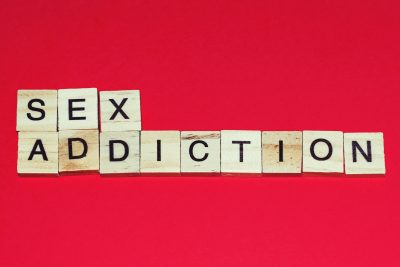 Wooden blocks on a red background spelling words Sex Addiction